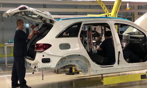 A worker assembling a vehicle at a factory operated by Beijing Benz Automotive.